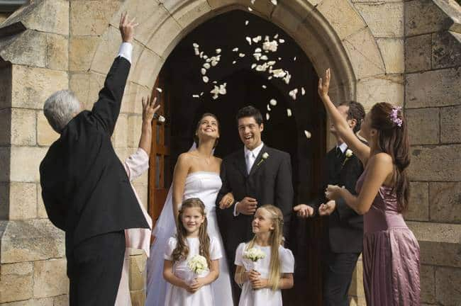 throwing flower petals over bride and groom