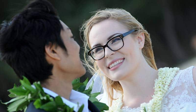 bride wearing her glasses lookin int the eyes of her love