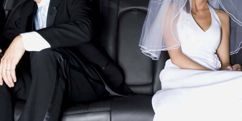 Close-up of a newlywed couple sitting in a car