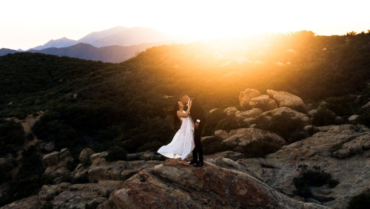 couple kissing on top of hill