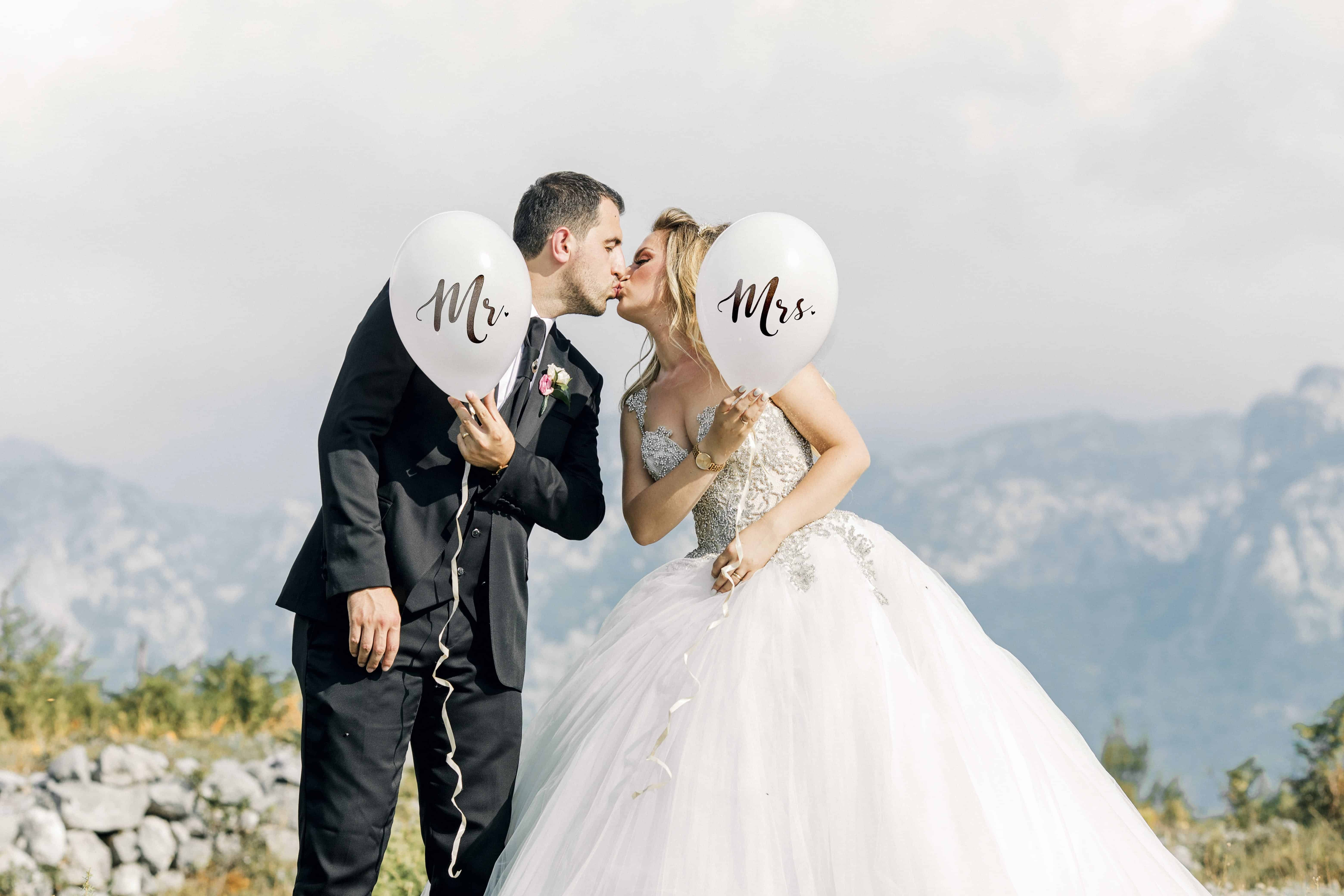 Man and Woman Kissing While Holding Balloons