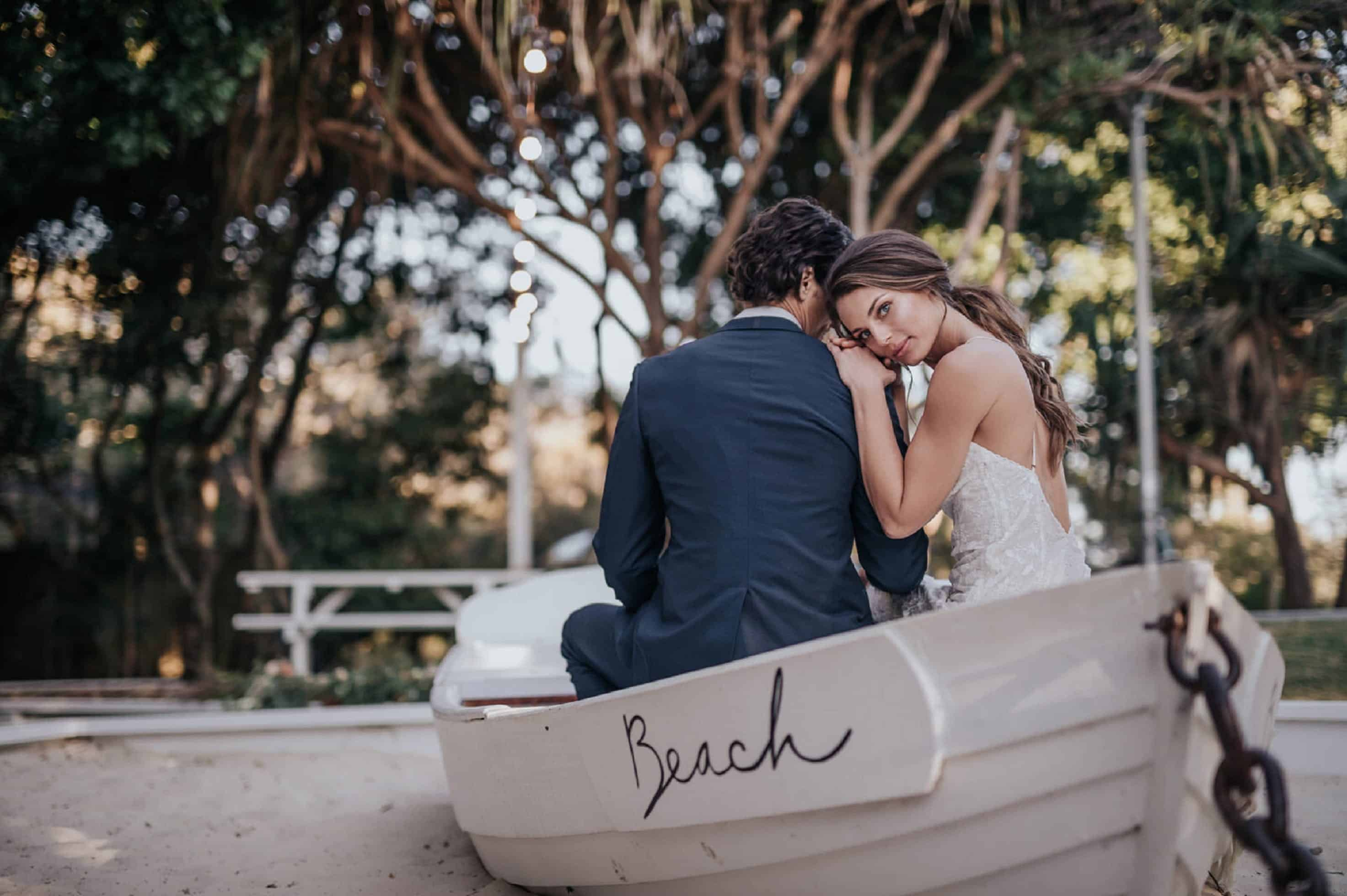 Man Wearing Blue Suit Jacket and Woman Wearing White Wedding Gown Sitting on White Canoe Boat