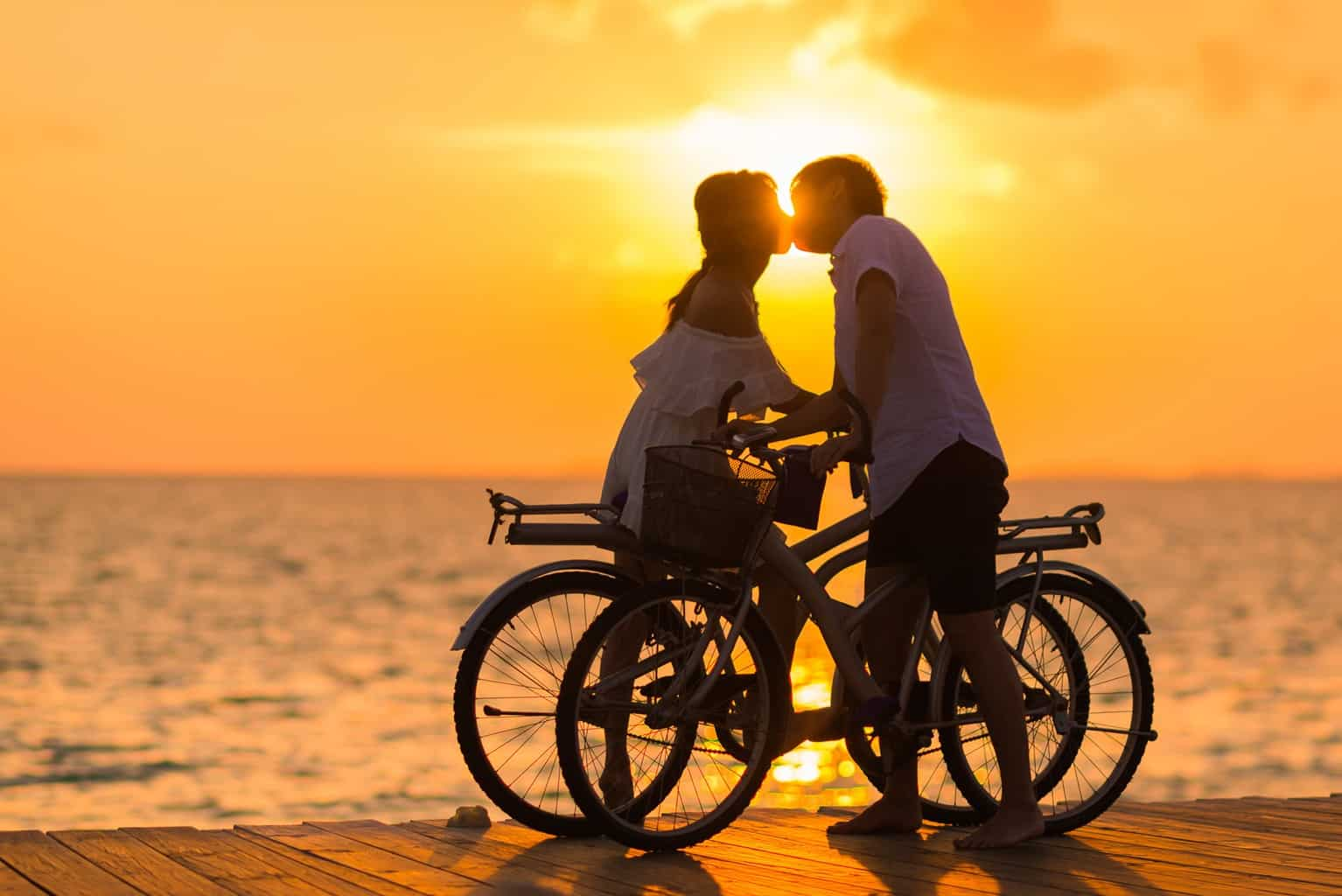 Photography of Man Wearing White T-shirt Kissing a Woman While Holding Bicycle on River Dock during Sunset