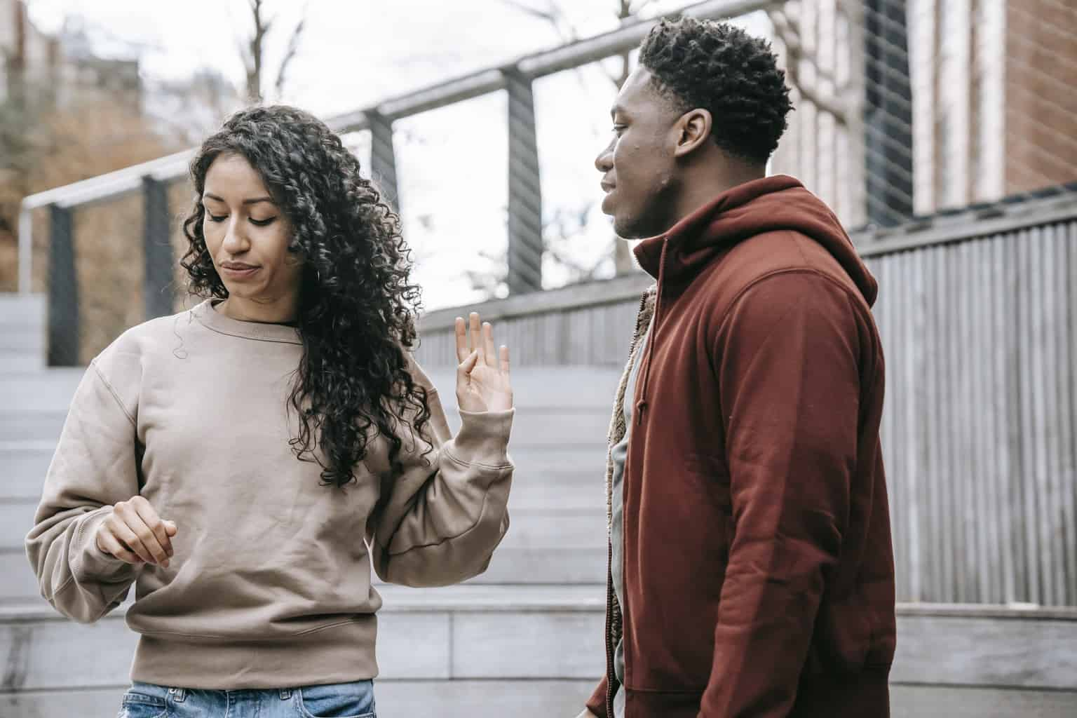 Upset ethnic girlfriend with raised hand and concerned African American boyfriend breaking up on street against metal grid on background