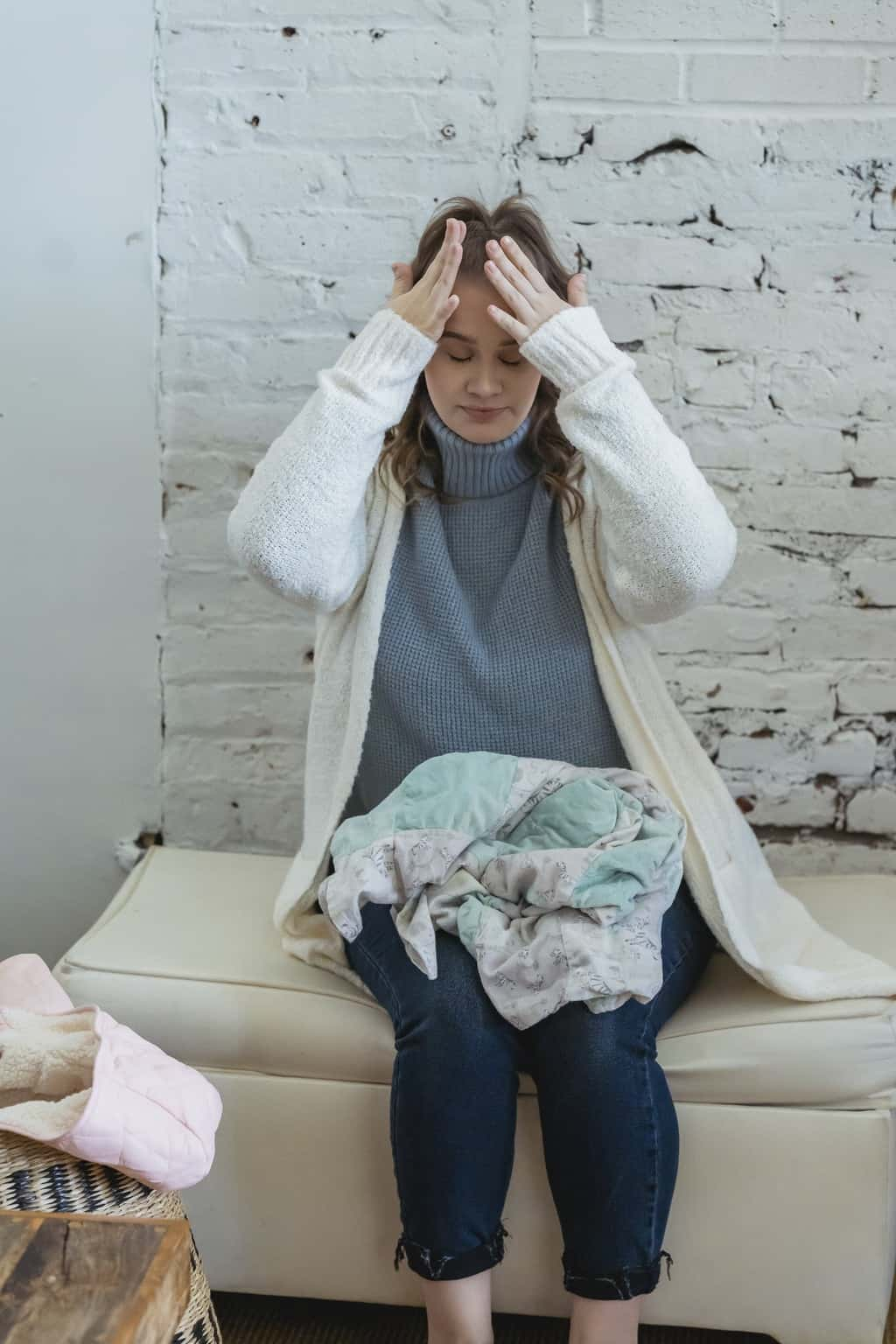 Exhausted female with closed eyes sitting on pouf near brick wall and suffering from headache