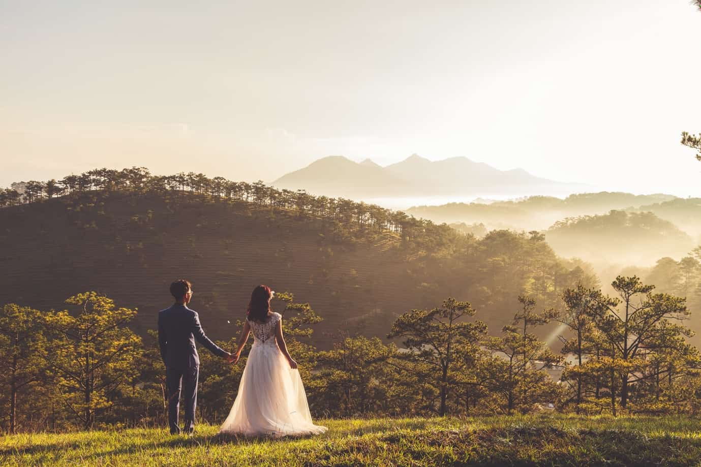 A person and person holding hands and walking in a field with trees and mountains in the background Description automatically generated with medium confidence